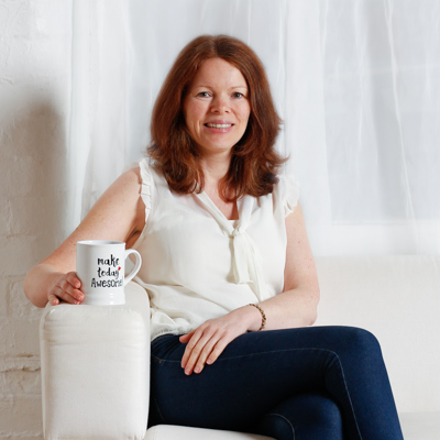 Smiling business woman in a branding portrait wearing a white top and jeans holding a cup